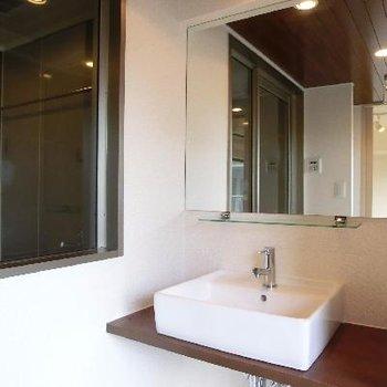 洗面台は光を浴びる。左手はバスルーム。仕切りもシースルー。