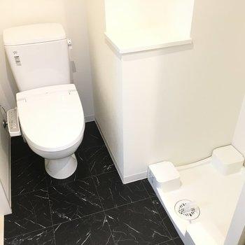 トイレと洗濯機置き場。黒の床がシックで格好良い。※写真は3階の同間取り別部屋のものです