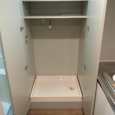 扉で隠せる洗濯機置き場は上に棚あり!