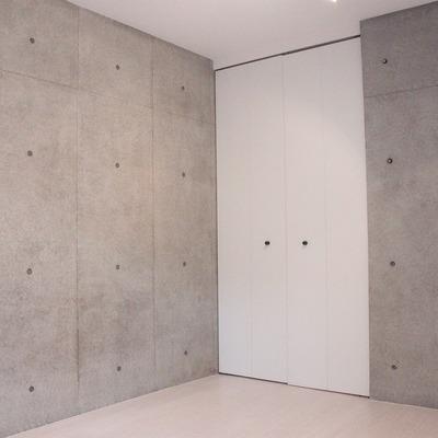 無機質なコンクリートの壁には、温かみのある色のフローリングをチョイス