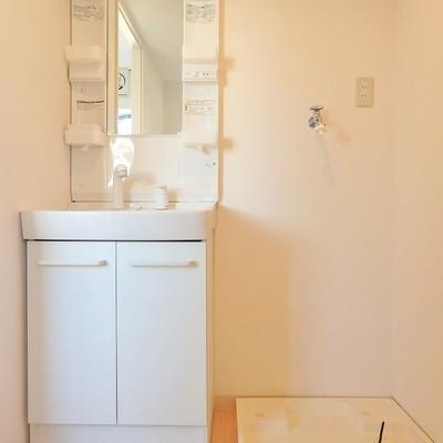 独立洗面台の横に洗濯機を置いて。