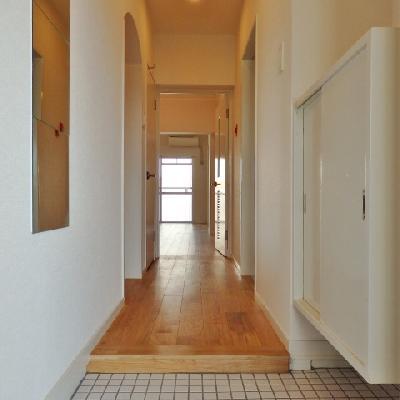 玄関は白タイル。姿見鏡とコート掛けがあります。