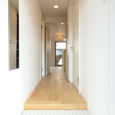 こだわりの白タイル玄関。姿見やコート掛けなども取り付けています