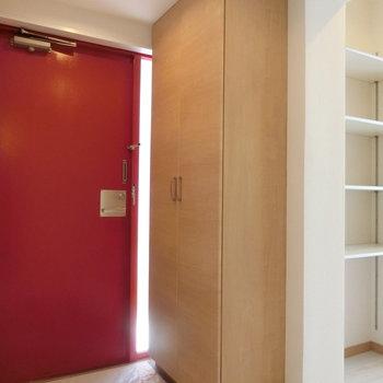 玄関の雰囲気。ドアは部屋側は赤色でした!! 隣には棚が。