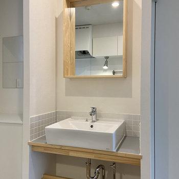 振り返るとタイルがかわいい独立洗面台。鏡の木枠はシェルフのように使うこともできますよ。