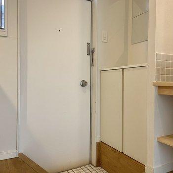 玄関はこんな感じ。白いミニタイル張りでお手入れもらくらくです。