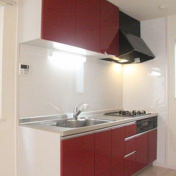 赤い鏡面仕上げのキッチンとのコントラストが映えます