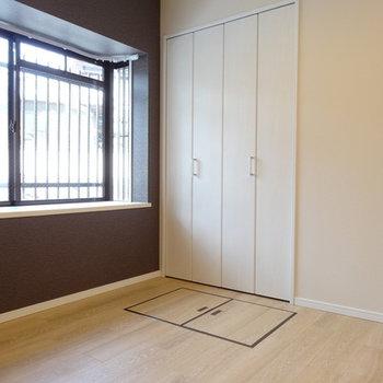 1つめの洋室は大きな出窓が。ブラウンの壁がアクセント。ん??床になにかあるぞ〜。
