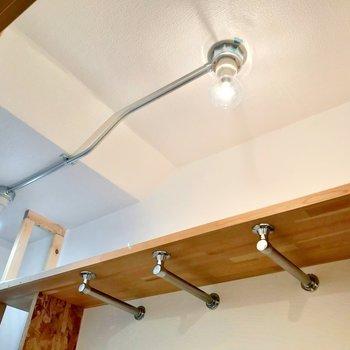 ハンガーポールが3本で棚つき。天井のライトもいい雰囲気。