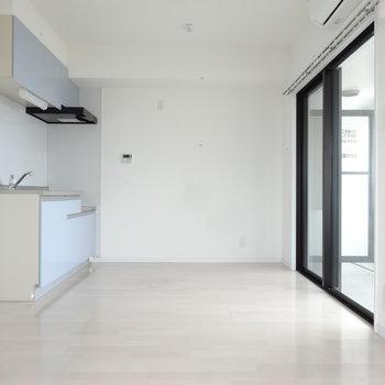 白の空間に優しいブルーのキッチンが。