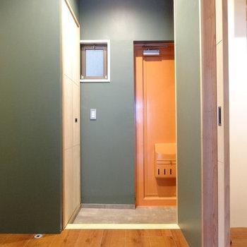 玄関スペースも広々しています。朱色の玄関ドアと深緑の壁が和モダンですね。