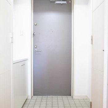 グレーのタイルとグレーのドアで、きれいめな玄関。