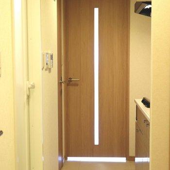 玄関入って右がキッチン。左がお風呂とトイレ※写真は4階の反転間取り別部屋のものです