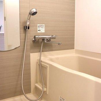 洗い場が広く、壁が木目のお風呂※写真は4階の反転間取り別部屋のものです