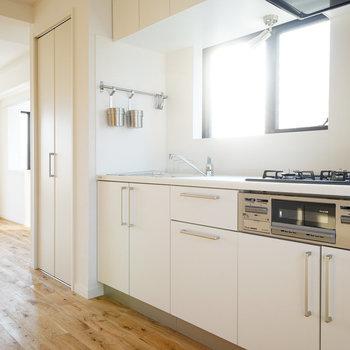 キッチンは大きな3口ガスコンロ※写真は同じ建物の別部屋です※実際はキッチン前の窓はございません