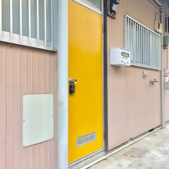 共用部は黄色いドアが目印!洗濯機置場もコチラです〜
