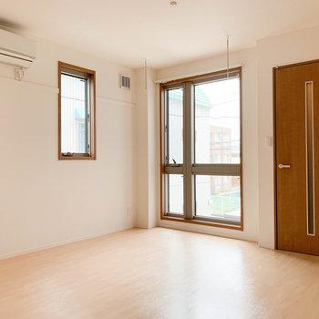 【下階】右の扉が玄関。大き窓で開放感のあるリビングです。