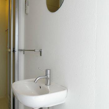 丸いミラーのついた洗面台。