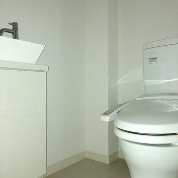 トイレにプチ洗面台があります。※写真は5階同間取り別部屋、通電前・清掃前のもので、一部フラッシュを使用しています。
