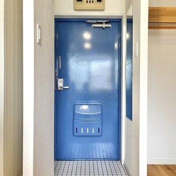 白いタイルとブルーの鮮やかな扉が印象的な玄関。