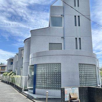 グレーのタイルの外装が特徴的な鉄筋コンクリートの建物。