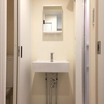 脱衣所に洗面台。鏡の裏に棚あります。