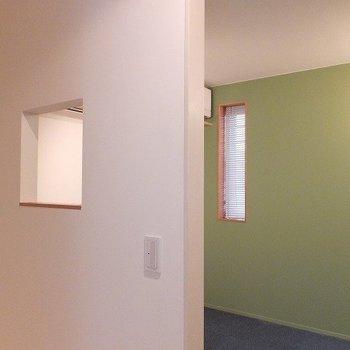 玄関を開けるとグリーンの寝室。*写真は別部屋です