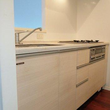キッチンは白っぽい淡い色。床の色を引き立てます。※写真は9階の反転間取り別部屋、清掃前のものです