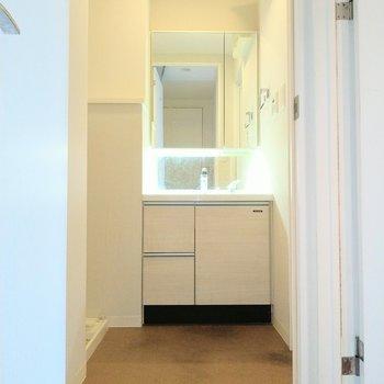 脱衣所には洗面台と洗濯機置場が隣合わせ※写真は9階の反転間取り別部屋、清掃前のものです