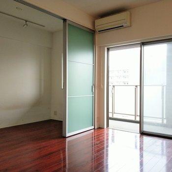 透ける引き戸の先は洋室※写真は9階の反転間取り別部屋、清掃前のものです