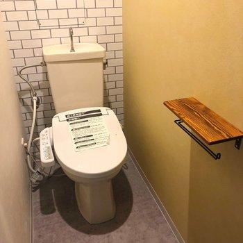 白タイルと黄色いアクセントクロスが可愛いトイレ※1階の反転の間取りの別部屋の写真です。