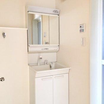 独立洗面台の隣に洗濯機です。脱衣所には床下収納もあります。※写真は前回募集時のものです。