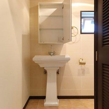 入って左手にキュートな洗面台。コンセントは鏡の中に(※写真は清掃前のものです)