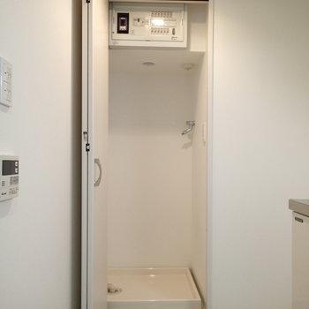 キッチンの奥に扉付きの洗濯機置場があります