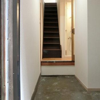 玄関は広々。段差を上がり、階段が。
