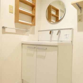 オシャレな洗面。木の棚と丸い鏡が優しげ。