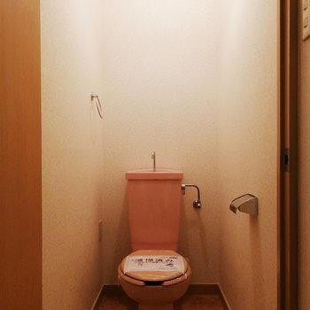 トイレはピンク!上に棚を設置して備品を置こう。