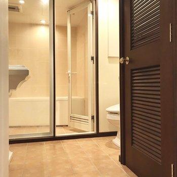 向かいには、ゴージャスなサニタリー。浴室はガラス張り。(※写真は6階の反転間取り別部屋、清掃前のものです)