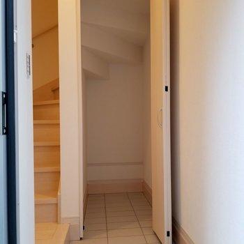 1階まで降りると玄関奥に収納が。階段の裏が見えてかわいい。