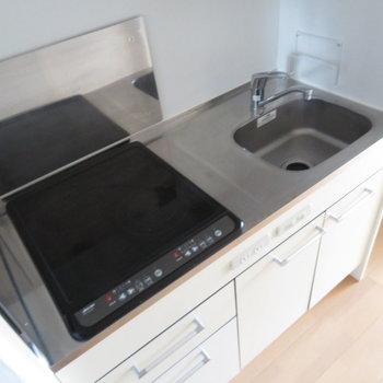 キッチンはIHの2口コンロ。実際は元気がでるオレンジ色!(※写真は10階の同間取り別部屋のものです)