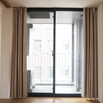 寝室、バルコニーを見る。※写真は6階同じ間取り別部屋のものです