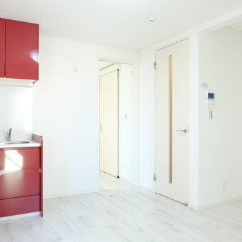 赤いキッチンがポイントのリビング