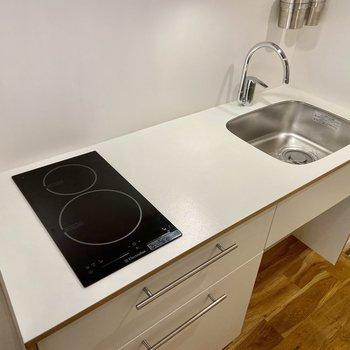 キッチンは二口IH。まな板のスペースもしっかりありますよ。