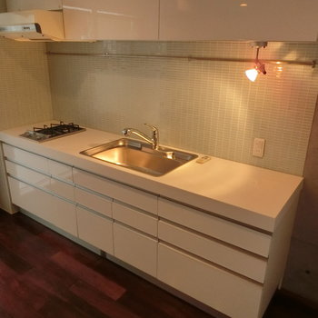 広々キッチン。薄水色のタイルがかわいげ