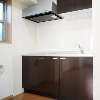 キッチンはダークブラウン。後ろに冷蔵庫を置きましょう。