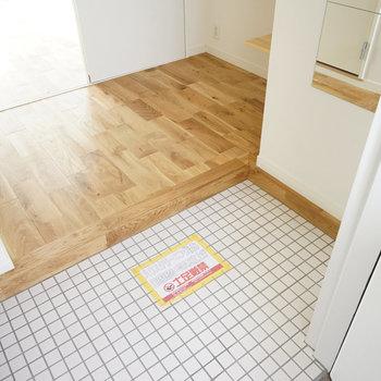 玄関は白いタイルで明るく清潔に