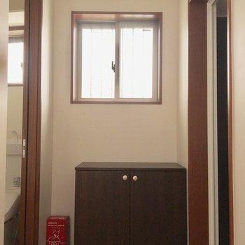 下駄箱の左側にトイレ、右側にお風呂です。※電気の付かない中での撮影です。