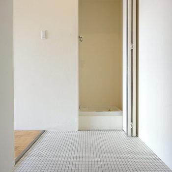 白タイルが素敵な玄関。に、隠せる洗濯機置き場。