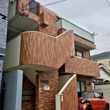 オレンジ色の鉄筋コンクリートマンションです。