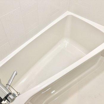 真っ白なお風呂場。湯船が広くなるように三角のような作りになっています。